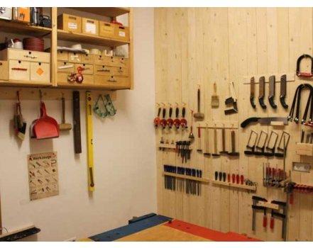 Ein kleiner aber schöner Werkstattraum mit Werkinsel, Materialregalen und Werkstattwand
