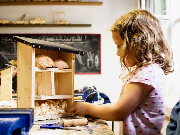 Ein Mädchen baut ein Insektenhotel aus Holz