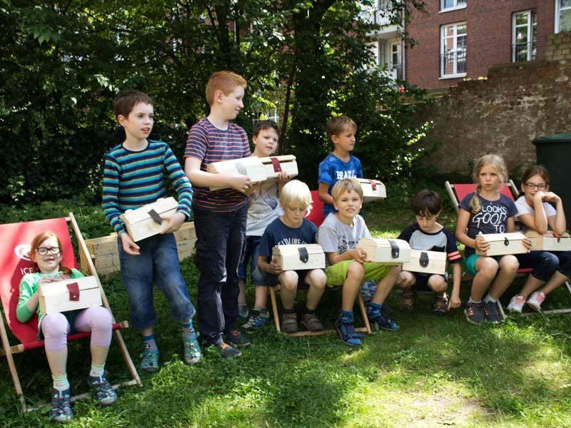 Pause im Garten Kinder mit ihren gebauten Schatzkisten