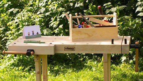 Kinderwerkbank im Garten mit Werkzeugset