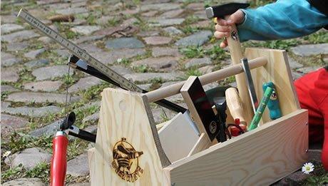 Kind holt Werkzeug aus dem Werkzeugkasten